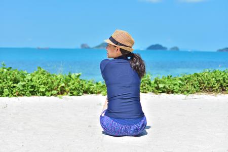 Woman sitting on white sand at sunny day and looking to somewhere Stock Photo