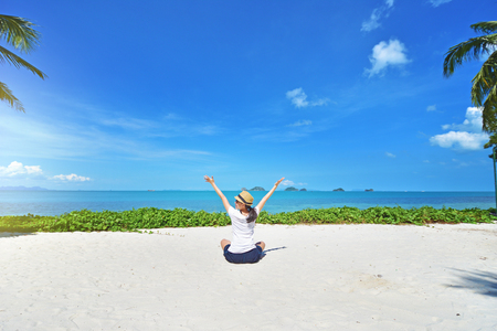 Freedom young woman with arms up outstretched to the sky with blue ocean landscape beach background Stock Photo