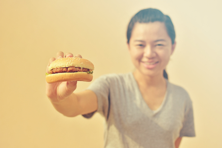 Smiling woman holding burger in hand, american unhealthy calories meal Stock Photo