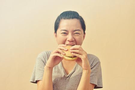 Woman is eating and enjoying  a fast food hamburger