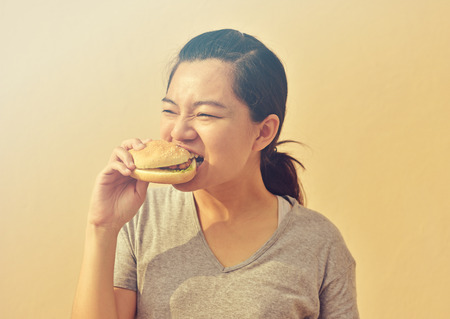 Young woman eat junk food burger in hand Stock Photo