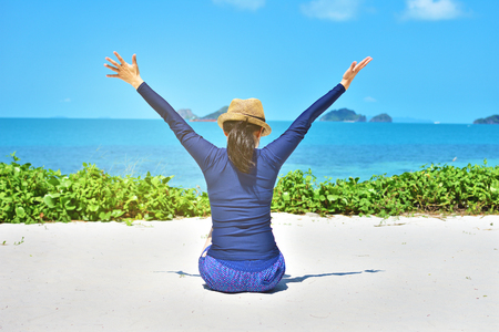 Happy woman arms open feeling freedom sitting on white sand and looking destinations beach Stock Photo