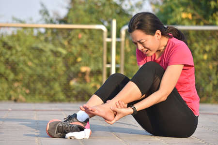 Female runner touching foot in pain due to sprained ankle Banque d'images