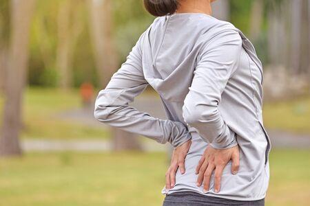 La giovane donna asiatica sente dolore alla schiena dopo aver fatto jogging. Archivio Fotografico