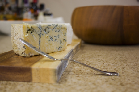 A cheese board with a wedge of blue cheese.