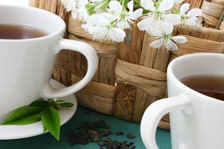 dwie filiżanki herbaty i suszonych liści herbaty