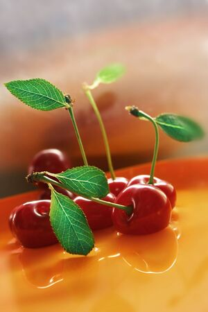 Red cherry with water, against various background