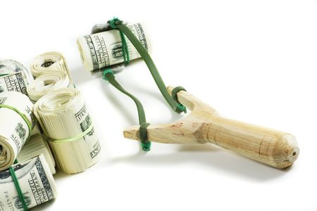 slingshot on white with rolls of money Stock Photo