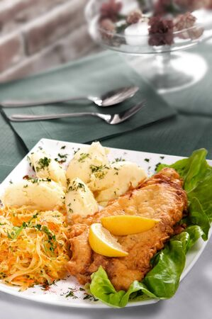 breaded chicken breast served with potatoes and lemon. Selective focus