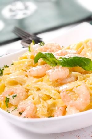 Prepared Shrimp with linguine noodles and creamy garlic sauce on top green basil spring. Selective focus. Stock Photo