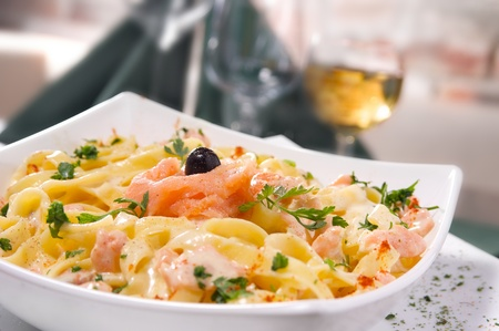Wild salmon in a cream sauce, served with linguini pasta. Selective focus.