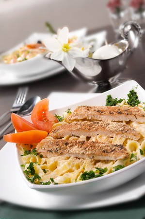 Classic creamy fettuccine alfredo topped with slices of grilled chicken breast. Stock Photo
