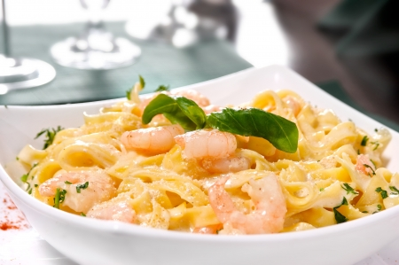 prepared shrimp: Prepared Shrimp with linguine noodles and creamy garlic sauce on top green basil spring. Selective focus. Stock Photo