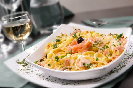 salmon dinner: Wild salmon in a cream sauce, served with linguini pasta. Selective focus.