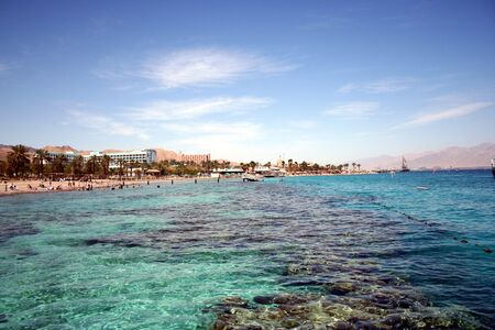 dive trip: View of Eilat from the sea, with buildings bathers, and mountains in background.