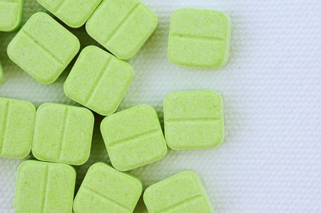 Green medicinal pills piled up a bunch of closeup isolate on white background.