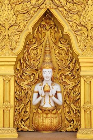 Angel statues on the walls. Golden angel. Art wall.