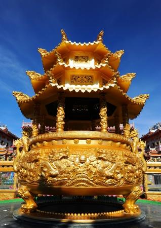 Big golden Incense burner on blue sky   Stock Photo