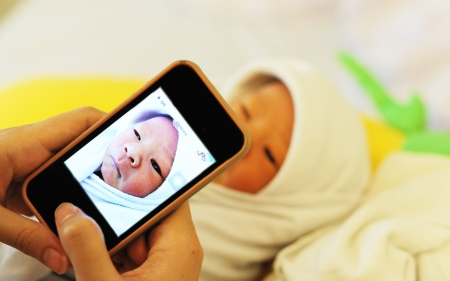 Mother use her mobile phone capture her new born baby   Stock Photo