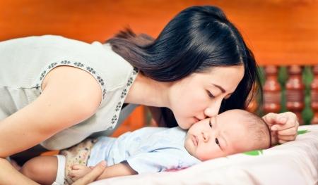 Beautiful mom holding her cute baby  Stock Photo