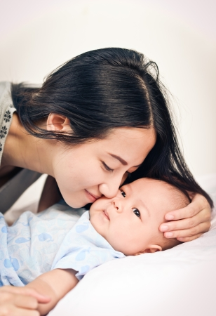 0 6 months: Beautiful mom holding her cute baby  Stock Photo