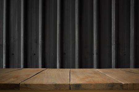 sheet steel: Wooden floor, wooden planks, wooden table with old black metal sheet, steel texture, steel pattern, steel wall in the dark.