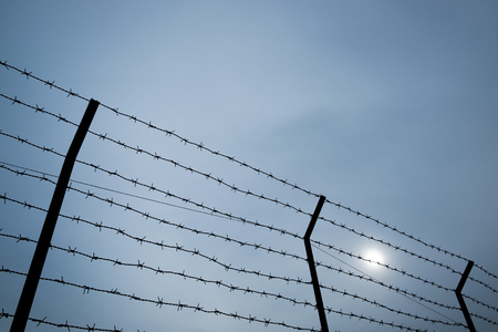 detention: Silhouette of barbed wire on the fence of the detention center with dark sky for background.