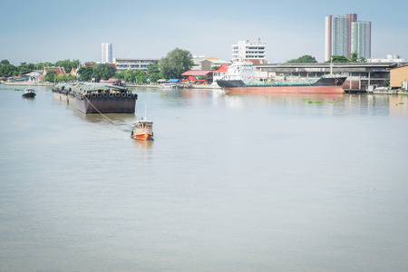 towed: A small tug boat towing a large sand tanker in the Chao Phraya River, bangkok, thailand.