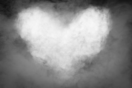 circular blue water ripple: Smoke heart shape in the dark with movement of smoke for background. Stock Photo