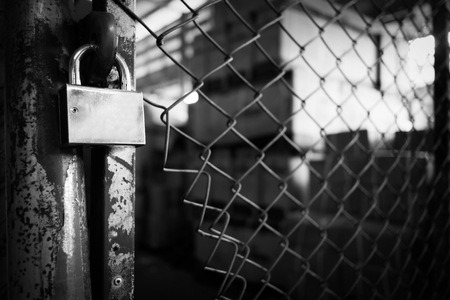 rusty wire: Selective focus on old lock on rusty wire fence with a low depth of field. black and white image. soft focus. noise scene. grain style. Stock Photo