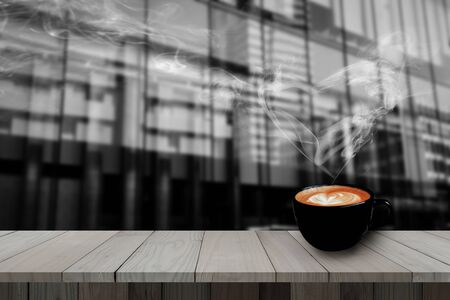 galvanized: Redolent cappuccino coffee with smoke heart shape on wooden table with blurred modern building. Stock Photo