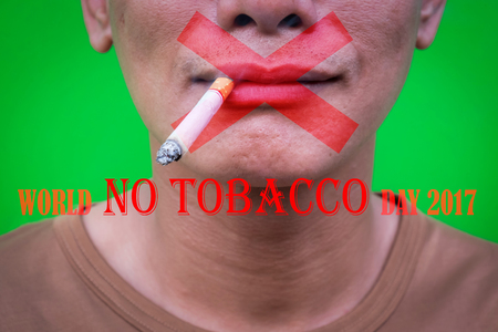 One asian man smoking on green background with texts world no tobacco day 2017. Selective focus.
