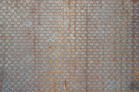 Old metal diamond plate or old checkered steel plate with rusty. Texture background.