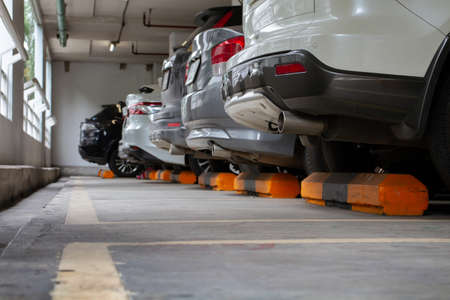 Cars parked in a line arranged in an orderly manner. Parking in a well-covered indoor parking lot To be orderly and prevent accidents effectively. 版權商用圖片