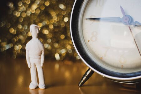 The puppet is like a small male statue made of white clay and an old clock against a blurred background of lights. Vintage or Retro style. Archivio Fotografico - 137409518