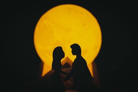 Young couple Young man and woman Are lovers, which are puppets made from clay in the darkness with the light of an artificial moon. Concept about Valentines day.