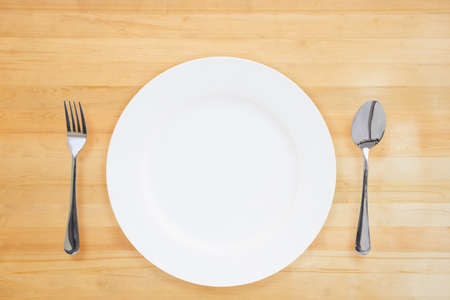 One blank white ceramic plate with a spoon and fork on a wooden floor or wooden table for placing pictures of food or food products.