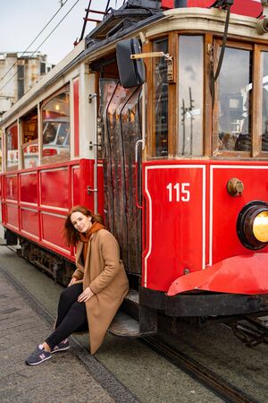 A girl with brown hair in a brown coat is sitting on the running Board of a redtram in the rain