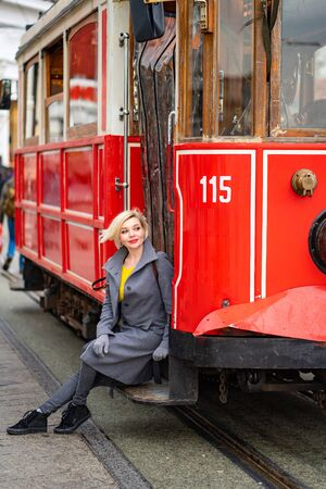 blond girl in a grey coat is sitting on the running Board of a redtram in the rain
