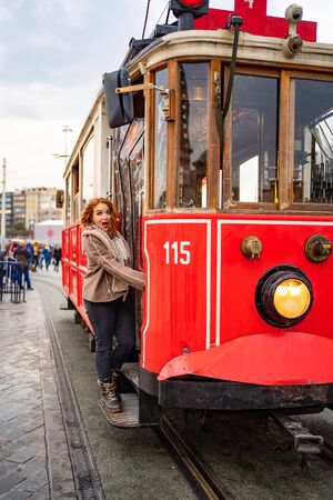 funny girl in a brown jacket is stand on the running Board of a redtram in the rain