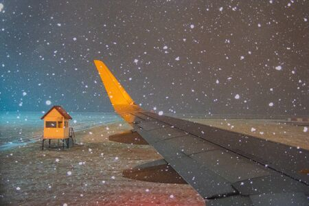 airplane wing in winter under snow at the airport at night on landing