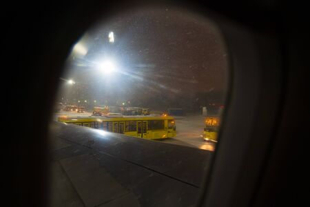 the yellow bus is waiting for passengers of the plane at night in winter, from the window