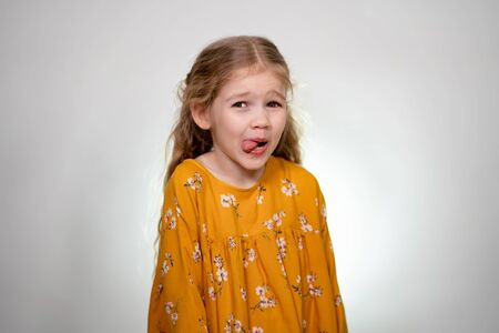 A little girl shows her tongue. Baby posing in a yellow dress on a white wall background.