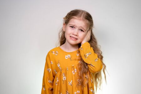 A little girl's sore ear and she holds his hand and cries. Babe posing in yellow dress on the white background of the wall.