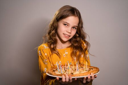 a teen blonde girl holding a pizza with candles on a white background. candles don't burn. Original birthday.