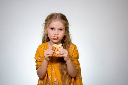 Little girl blonde laughing and chewing on a delicious piece of pizza on white background