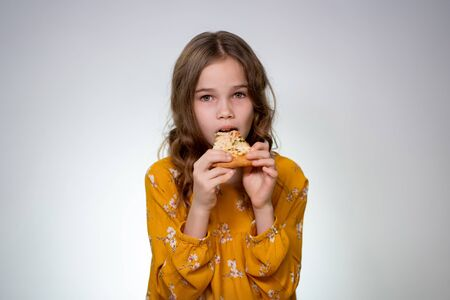 Teenager girl with curly hair biting and eating pizza on a white background. Delicious food. Fast food. Foto de archivo