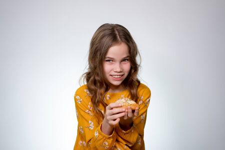 A teenage girl with curly hair Holds a slice of pizza on a white background. Delicious food.