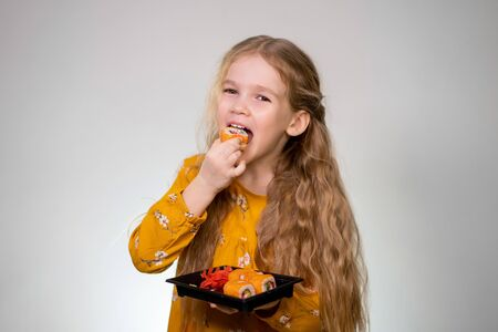 Little girl bites tasty rolls and holds in hands. Japanese cuisine home delivery. Delicious. White background. Long hair, yellow dress