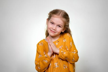 Beautiful little girl blonde folds his arms like an angel, smiling sweetly and looking at the camera. Yellow dress. White background.